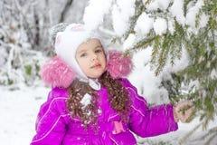Маленькая девочка тряся ветвь сосны покрытую снегом Стоковые Фото