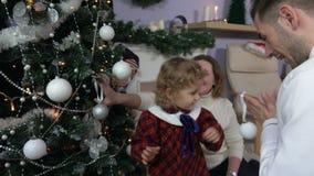 Маленькая девочка украшает рождественскую елку видеоматериал