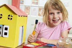 Маленькая девочка украшая модельную дом внутри помещения Стоковые Фотографии RF
