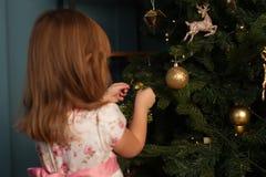 Маленькая девочка украшая рождественскую елку с игрушками стоковое фото