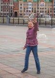 Маленькая девочка улавливает пузыри мыла в улице Стоковое Фото
