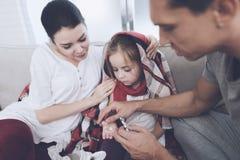 Маленькая девочка уловила холод Ее мать и отец обрабатывают ее Отец дает девушке пилюльку Стоковые Изображения RF