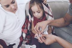 Маленькая девочка уловила холод Ее мать и отец обрабатывают ее Отец дает девушке пилюльку Стоковые Фото