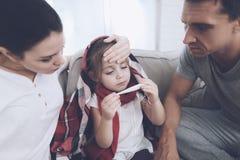 Маленькая девочка уловила холод Ее мать и отец обрабатывают ее Девушка смотрит термометр Стоковое Фото