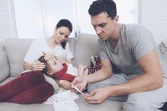 Маленькая девочка уловила холод Ее мать и отец обрабатывают ее Девушка лежит на ее подоле ` s матери Стоковые Фото