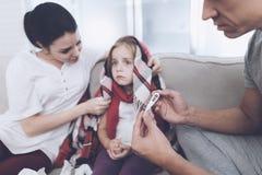 Маленькая девочка уловила холод Ее мать и отец обрабатывают ее Отец измеряет температуру ` s девушки Стоковое Изображение