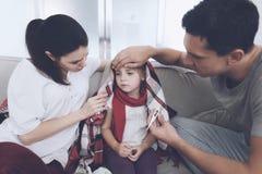 Маленькая девочка уловила холод Ее мать и отец обрабатывают ее Отец измеряет температуру ` s девушки Стоковые Фотографии RF