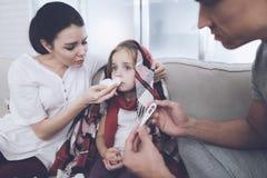 Маленькая девочка уловила холод Ее мать и отец обрабатывают ее Отец измеряет температуру ` s девушки Стоковые Изображения RF