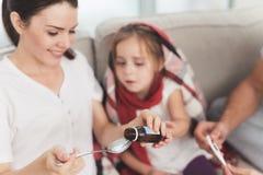 Маленькая девочка уловила холод Ее мать и отец обрабатывают ее Мать льет сироп девушки в ложку Стоковая Фотография RF