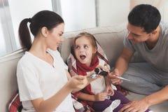 Маленькая девочка уловила холод Ее мать и отец обрабатывают ее Мать льет сироп девушки в ложку Стоковая Фотография