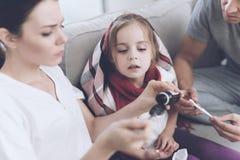 Маленькая девочка уловила холод Ее мать и отец обрабатывают ее Мать льет сироп девушки в ложку Стоковые Изображения RF