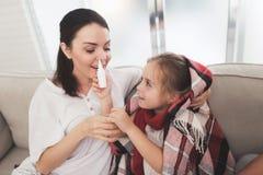Маленькая девочка уловила холод Ее мать обрабатывает ее Девушка squirts ее мать в носе с носовым брызгом Стоковое фото RF