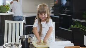 Маленькая девочка улыбки замешивая тесто l в большом стекле шара в кухне Счастливая небольшая девушка в кухне Ребенок акции видеоматериалы