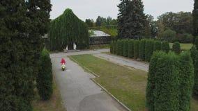 Маленькая девочка управляет самокатом outdoors Снятый на трутне акции видеоматериалы