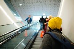Маленькая девочка управляя вверх на эскалаторе в торговом центре стоковое изображение