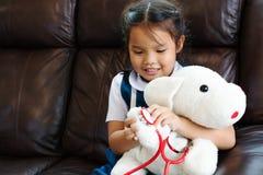 Маленькая девочка усмехающся и играющ доктора с стетоскопом Ребенк и концепция здравоохранения стоковая фотография
