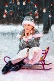 Маленькая девочка усмехаясь в лесе Нового Года на скелетоне Девушка снега в праздничном костюме Зима, снег понижается Игрушки на  стоковые фото
