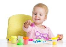 Маленькая девочка уча использовать красочное тесто игры на белой предпосылке стоковые фотографии rf