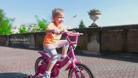 Маленькая девочка учит ехать на велосипеде акции видеоматериалы