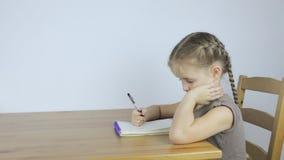 Маленькая девочка учит и пишет назначения в тетради сток-видео