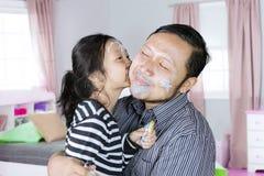 Маленькая девочка целует ее отца в спальне Стоковая Фотография RF