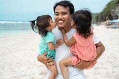 Маленькая девочка 2 целуя совместно к его отцу на пляже стоковая фотография rf