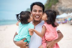 Маленькая девочка 2 целуя совместно к его отцу на пляже стоковые фото