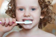 Маленькая девочка чистя ее зубы щеткой стоковые фото