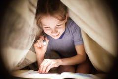 Маленькая девочка читает книгу под одеялом с электрофонарем в темной комнате на ноче Стоковые Изображения