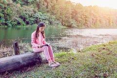 Маленькая девочка читая книгу в парке стоковые изображения rf