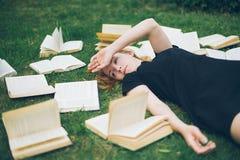 Маленькая девочка читая книгу пока лежащ в траве Девушка среди книг в саде лета стоковое фото rf
