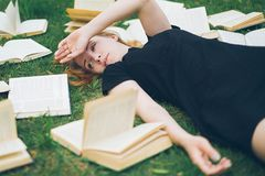 Маленькая девочка читая книгу пока лежащ в траве Девушка среди книг в саде лета стоковые фотографии rf