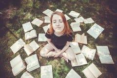 Маленькая девочка читая книгу пока лежащ в траве Девушка среди книг в саде лета стоковая фотография