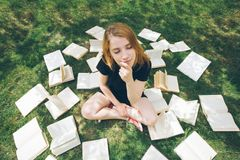 Маленькая девочка читая книгу пока лежащ в траве Девушка среди книг в саде лета стоковое фото