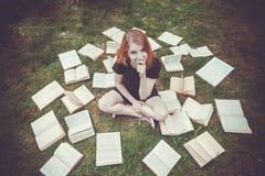 Маленькая девочка читая книгу пока лежащ в траве Девушка среди книг в саде лета стоковое изображение