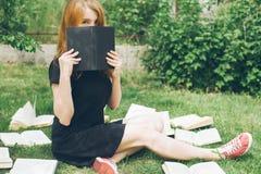 Маленькая девочка читая книгу пока лежащ в траве Девушка среди книг в саде лета стоковые фото