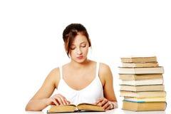 Маленькая девочка читая около кучи книг. Стоковые Фотографии RF