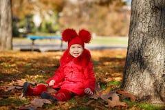 Маленькая девочка штыря-вверх тележки toothsome нося красную blushful куртку зимы и теплая шляпа с ботинками фасонируют стильные  Стоковые Фотографии RF