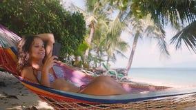 Маленькая девочка Atractive в бикини используя мобильный телефон беседуя в гамаке на пляже около моря и пальмы медленно видеоматериал