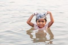 Маленькая девочка Bru племени усмехающся и использующ шампунь пока принимающ ливень в Меконге в жаркой погоде лета Деревня Bru, стоковое фото rf