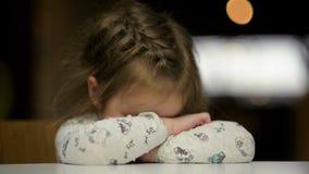Портрет грустной девушки кладя ее голову на стол Маленькая девочка Cutie идет заплакать акции видеоматериалы