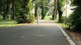 Маленькая девочка skateboarding на солнечный день в парке видеоматериал
