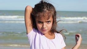 Маленькая девочка tidying ее волосы на ветре акции видеоматериалы