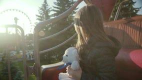 Маленькая девушка едет на карусели, смотрит и поворачивает вокруг с ее плюшевым медвежонком на заходе солнца в slo-mo сток-видео