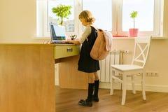 Маленькая девушка студента 8 лет в школьной форме с рюкзаком использует компьтер-книжку Школа, образование, знание и дети стоковое фото