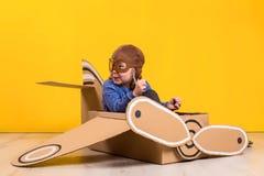 Маленькая девушка фантазера играя с самолетом картона Детство Фантазия, воображение стоковые изображения