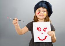 Маленькая девушка художника с drwan улыбкой изолированная на сером цвете стоковое фото