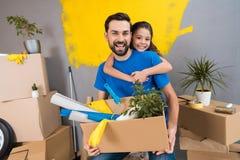 Маленькая дочь обнимает ее отца, который держит коробку инструментов и вещей Семья расквартировывает ремонты совместно стоковое фото
