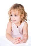 Маленькая заботливая девушка сидя на таблице Стоковая Фотография