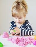 Маленькая кавказская девушка играя с розовым кинетическим песком дома Стоковая Фотография RF